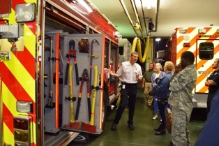 A firefighter showing a group of citizens the tools on the fire truck
