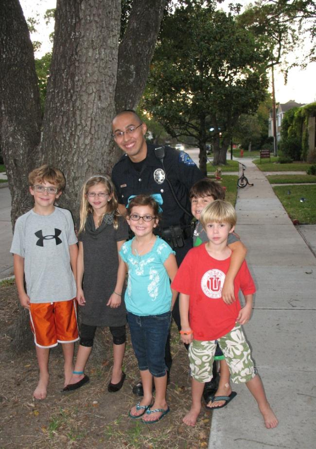 A police officer and a group of young children stand next to a tree