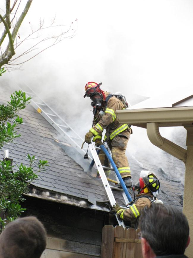 Firefighter on top of roof filled with smoke
